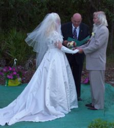 Senior Christians marry while holding hands and facing each other with the pastor giving his blessing