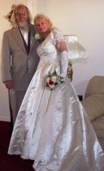 A woman in her wedding dress leans into her husband who looks very pleased