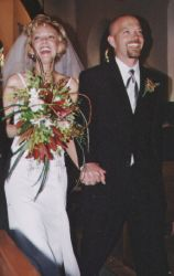 New Christian bride laughs while holding her flowers and her new husband's hand