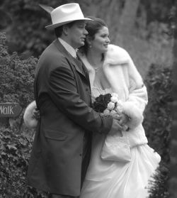 Fashionable wedding for a man in hat and his beautiful wife in furs