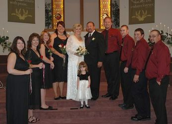 Large wedding party poses with bride and groom at church