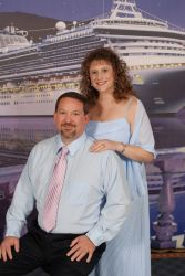 A well dressed couple stand and smile in front of a cruise ship