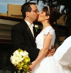 Beautiful Christian bride kisses her sweetheart while holding bridal bouquet