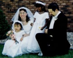 Blended Christian family laugh together at the wedding