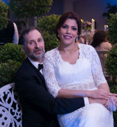 Smiling bride from Dominican sitting with husband who holds her affectionately