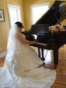Bride plays piano in her wedding dress