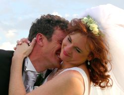 A very happy groom laughs and buries his head in his bride's shoulder as she smiles