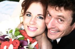 A smiling Christian man sits behind a beautiful woman holding flowers