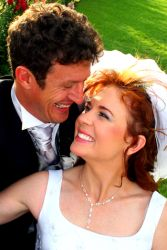 A couple laugh for joy outdoors after marrying