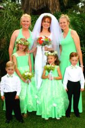 A bride in white is surrounded by her bridesmaids in green