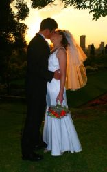 A couple kiss while silhouetted in the setting sun