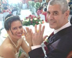 Married couple lean back and laugh while showing off their wedding rings