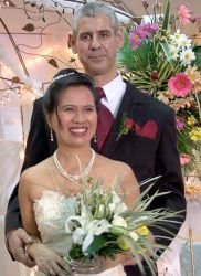 A tall Christian man stands behind his beautiful Filipina wife